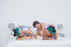 Girls in hair rollers having fun in bed Stock Photos