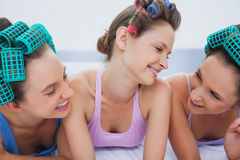Girls in hair rollers relaxing in bed and talking Royalty Free Stock Photography