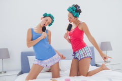 Girls in hair rollers singing with hairbrush Royalty Free Stock Photos