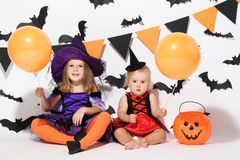 Girls in halloween costumes. Little girls in halloween costumes with balloons sitting on white background stock images