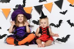 Girls in halloween costumes. Little girls in halloween costumes sitting on white background royalty free stock images