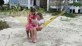 Girls in the hammock with the tablet on the beach. Two young girl relaxing on hammock and using digital tablet.girls in a hammock on a tropical beach and playing stock footage