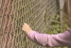 Girls hand holding a fence Royalty Free Stock Photo