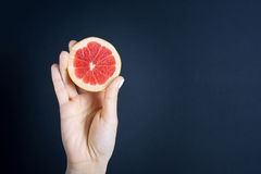 Girls hand holding a halved grapefruit Stock Photos