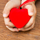 Girls hand holding  a red heart shape. Stock Image