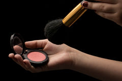 Girls hand with make-up. Brush and rouge on dark background royalty free stock image