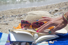 Girls hand reaching for sunglasses and a book on the beach with Stock Photo