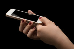 Girls hand with smartphone. On dark background royalty free stock photos