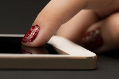 Girls hand with smartphone. On dark background stock images