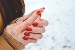 Girls hands in cold in winter day. Girls hands цшер red manicure in cold in winter day Royalty Free Stock Image