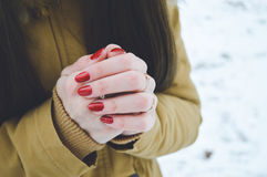 Girls hands in cold in winter day. Girls hands цшер red manicure in cold in winter day Royalty Free Stock Photo