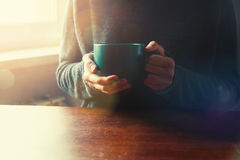 Girls hands with cup of coffee or tea. In morning light stock image