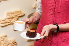 Girls hands hold a cup of coffee and cake Stock Photo