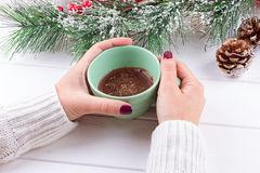 Girls Hands Holding Hot Chocolate on White Table with Christmas decorations Stock Image