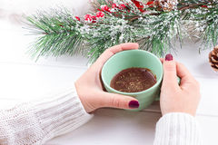 Girls Hands Holding Hot Chocolate on White Table with Christmas decorations Stock Photo