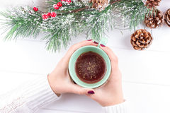 Girls Hands Holding Hot Chocolate on White Table with Christmas decorations Royalty Free Stock Photos