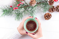 Girls Hands Holding Hot Chocolate on White Table with Christmas decorations Royalty Free Stock Images