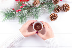 Girls Hands Holding Hot Chocolate on White Table with Christmas decorations Stock Images