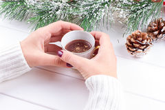 Girls Hands Holding Hot Chocolate on White Table with Christmas decorations Stock Photos