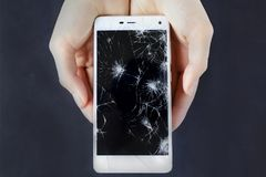 Girls hands holding a phone with broken screen. Girls hands holding a smart phone with broken screen stock images