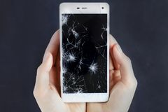 Girls hands holding a phone with broken screen. Girls hands holding a smart phone with broken screen stock image
