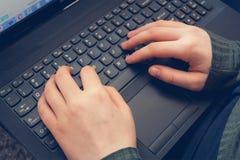 Girls hands on laptop keyboard, close up shot. Girls hands on laptop keyboard in the house, close up shot Stock Images