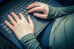 Girls hands on laptop keyboard, close up shot. Girls hands on laptop keyboard in the house, close up shot Stock Photo