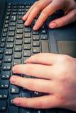 Girls hands on laptop keyboard, close up shot. Girls hands on laptop keyboard in the house, close up shot Royalty Free Stock Image