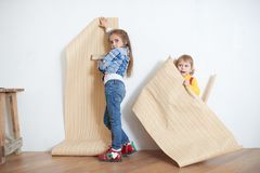 Girls hanging wallpaper. Decorating the wall. Cute little girls hanging wallpaper. Decorating the wall stock images