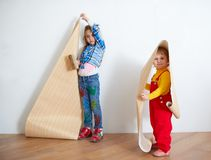 Girls hanging wallpaper. Decorating the wall Royalty Free Stock Photo