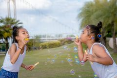 Girls happiness funny soap bubble in the park ,Laughing happy wi royalty free stock photography