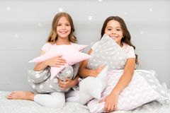 Girls happy best friends or siblings in cute stylish pajamas with pillows sleepover party. Sisters play pillows bedroom stock photo