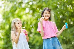 Girls are happy about the soap bubbles. Two girls are happy about the floating soap bubbles in nature Stock Photography