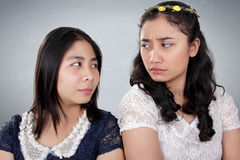Girls hatred. Two Asian girls in bad situation, looking against each other with hateful stares, over grey background Stock Photos