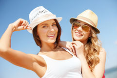 Girls in hats on the beach Stock Photos