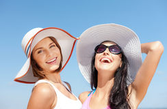 Girls in hats on the beach stock images