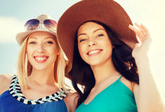 Girls in hats on the beach royalty free stock images