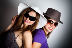 Girls in hats and sunglasses Stock Images