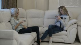 Girls have conversation without talking. Two girls discuss something using their phones stock video