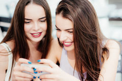 Girls have fun with a phone in coffee Royalty Free Stock Image