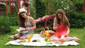 Girls Have a Picnic, Eat and Read a Book. 2 Girls Have A Picnic In A Garden, On A Beautiful Spring Day stock footage