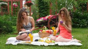 Girls Have a Picnic and Read a Book. 2 Girls Have A Picnic In A Garden, On A Beautiful Spring Day stock video footage