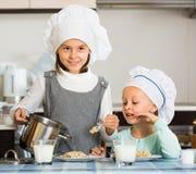 Girls having breakfast with porridge Stock Photos