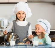 Girls having breakfast with porridge Stock Images