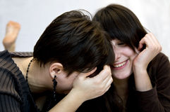 Girls having fun. Girls laughing while lying on the floor Stock Photography