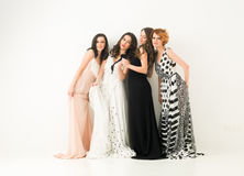 Girls having fun. Beautiful caucasian women in cocktail dresses posing together and having fun, against white background Royalty Free Stock Images