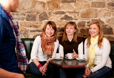 Girls are having fun in cafe. Man just arrived in a caffee where three girls were expecting him Stock Image