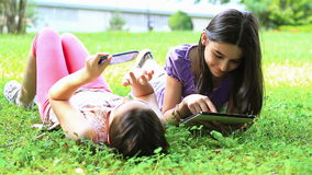 Girls having fun on digital tablet and smartphone. Outdoors stock video