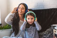 Mother and daughter having fun at home listening music Stock Images