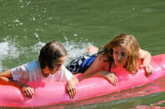 Girls having fun on inflatable Stock Images